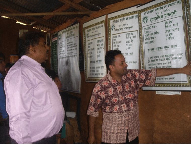 Auditors at the CFUG office observing records and displays (Indu Sapkota in check shirt, Rajmani Mishra in white)