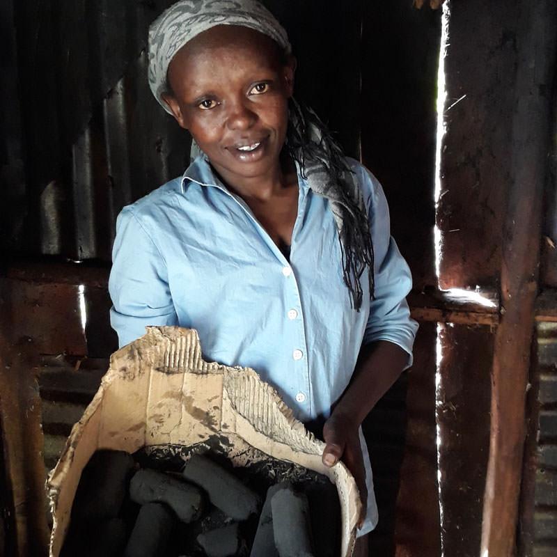 Kenyan tea farmer holding bio briquettes.