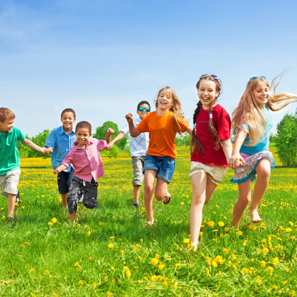 Kids running in grass - header